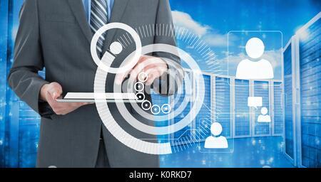 Digital composite de business man holding a tablet et graphiques in server room Banque D'Images