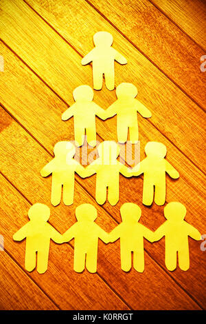 High angle view of paper cut out figures formant pyramide humaine sur la table Banque D'Images