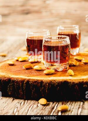 Amaretto liqueur italienne en tasses d'amandes sur une table en bois, selective focus