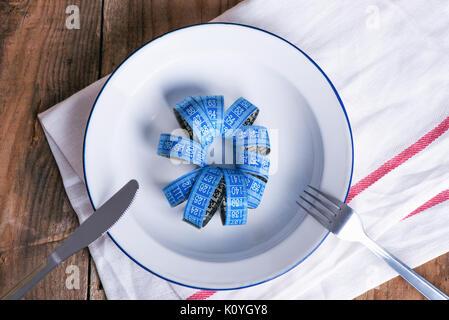Concept L'alimentation et la perte de poids. La plaque vide avec un ruban à mesurer au milieu de la plaque Banque D'Images