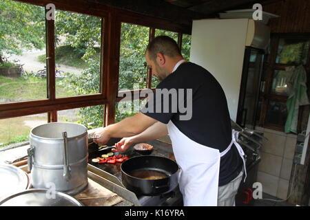 Un homme avec un tablier de préparer des aliments dans la cuisine Banque D'Images