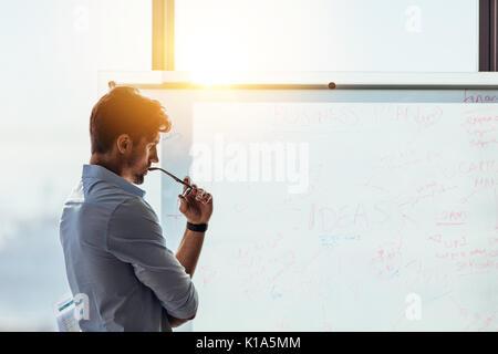 Investisseur dans l'entreprise à la réflexion profonde à l'idées d'affaires écrit sur le tableau blanc. La pensée Banque D'Images