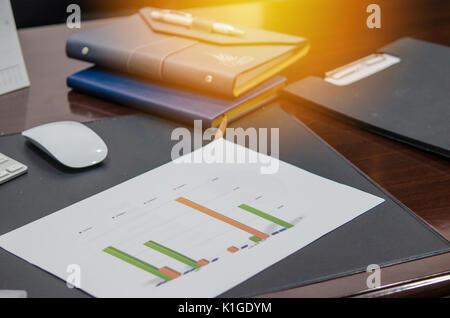 Des documents, des graphiques et de la souris sur le bureau de l'ordinateur portable Banque D'Images