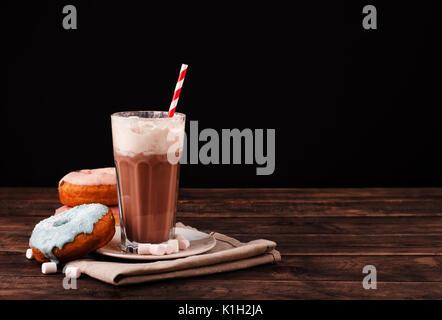 Milkshake avec beignes et d'autres bonbons sur un fond sombre avec un espace réservé au texte