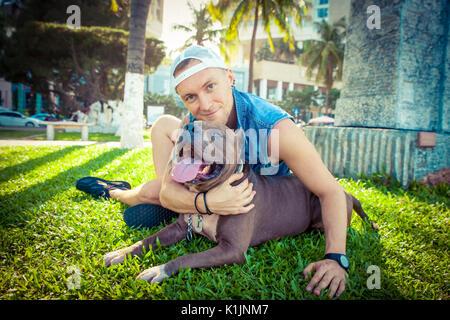 L'homme et le chien bull-terrier américain de mine de détente à l'initiative Faire place au parc et s'étreindre Banque D'Images