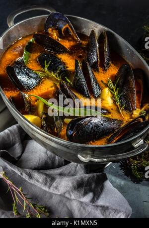 Les moules fruits de mer soupe de tomate en pot métal, fond gris Banque D'Images