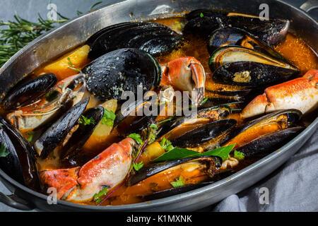 Soupe de fruits de mer crabes moules en chaudron, fond gris Banque D'Images