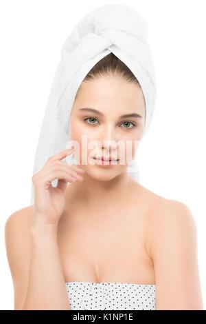 Belle jeune femme brune avec visage propre et une serviette sur sa tête. Isolées. Banque D'Images
