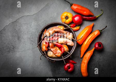 L'Amérique latine traditionnelle escabeche - piment fermentée. Piment épicé mariné au vinaigre. Fond d'Ardoise Banque D'Images