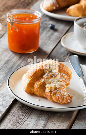 Petit déjeuner croissant, confiture en pot et tasse de café sur la table en bois. vertical, selective focus Banque D'Images