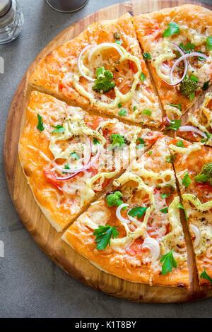 Pizza végétarienne sur fond de béton rustique. Italian Pizza aux légumes et fromage de près. Banque D'Images