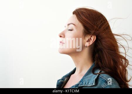 Portrait d'une belle femme rousse. Elle a l'air loin dans une façon inspirée, rêvant de quelque chose. Banque D'Images