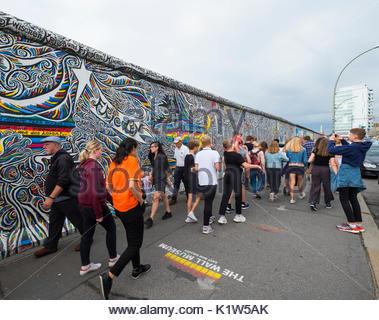 De nombreux touristes à pied passé peint murale sur l'article original du mur de Berlin à l'East Side Gallery à Banque D'Images