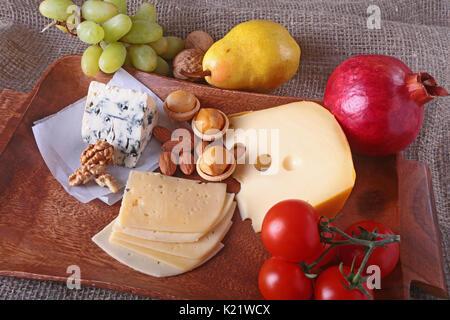 Assortiment de fromage avec fruits, raisins et noix sur un plateau de service en bois