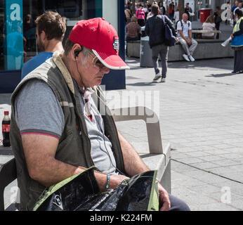 Homme assis sur un banc de travail avec écouteurs, écouter de la musique. Liverpool, Angleterre, Royaume-Uni Banque D'Images
