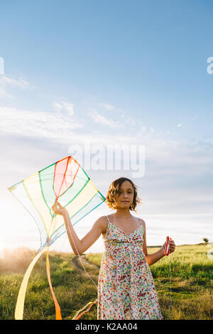 Girl holding kite et fonctionnant dans le champ