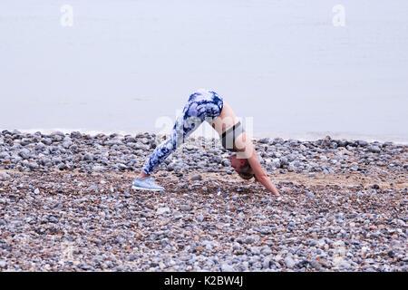 Jeune femme passe chien tête en bas, une position de yoga, sur la plage de Cromer, Norfolk, Royaume-Uni. Banque D'Images