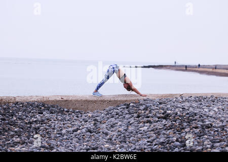 Young woman doing yoga on sea wall en Cromer, Norfolk, Royaume-Uni.