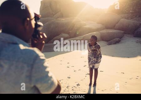 Jeune homme de prendre photo de sa petite amie. Belle femme qui posent pour la prise de photo sur mer. Banque D'Images