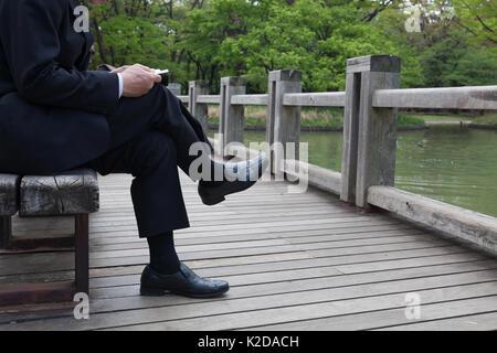Un homme en costume est assis les jambes croisées sur un banc dans un parc pour lire un livre. lire un livre. Parc Banque D'Images