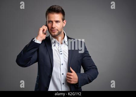 Un certain beau jeune homme élégant en conversation sur un smartphone Banque D'Images