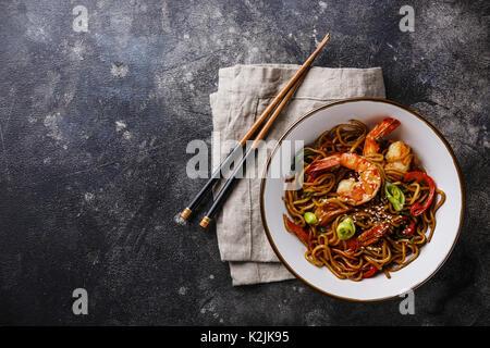 Les nouilles Udon sautés avec légumes et crevettes Tiger dans un bol sur fond sombre copy space Banque D'Images