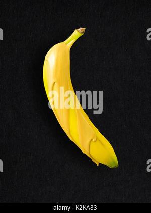 Concept créatif photo d'une banane recouverte de peinture or sur fond noir. Banque D'Images