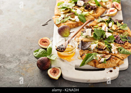 Pizza d'automne pain plat avec vinaigre balsamique, figues, fromage et salade Banque D'Images