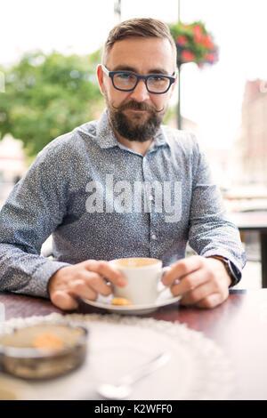 Homme barbu assis dans un café-jardin et avoir cappuccino Banque D'Images