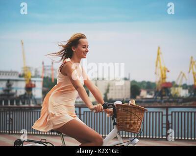 Piscine fashion portrait of smiling blonde dame équitation son vélo vintage retro hipster en robe élégante. Vivez Banque D'Images