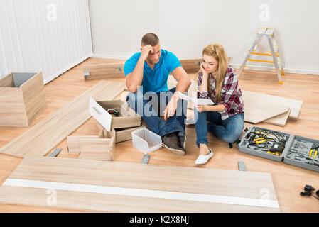 Portrait de couple envisagées avec des meubles démontés en pièces Nouvelles Home Banque D'Images