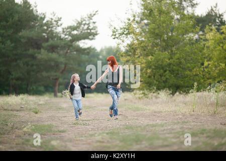 Happy girl avec sa mère rire fun, tenir la main et courir le long de la route forestière sur marche. Banque D'Images