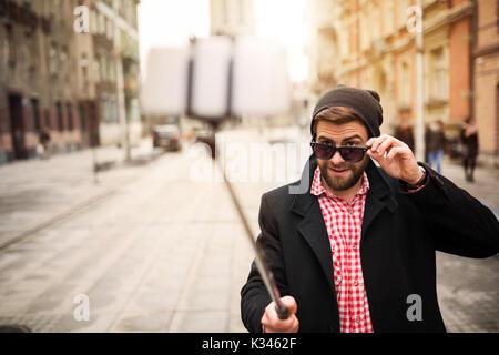 Une photo de l'homme jeune et branché en prenant lui-même une photo de son téléphone mobile.