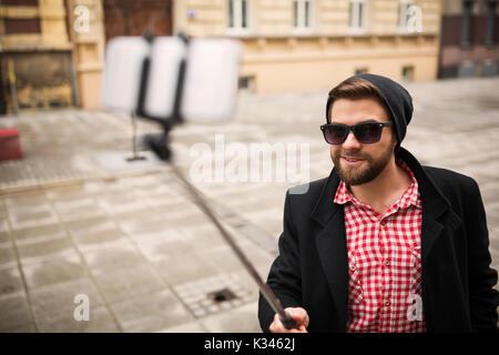 Une photo du jeune homme confiant en lui-même une photo de son téléphone mobile.