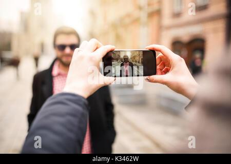 Une photo de fille en prenant une photo de jeune homme par son téléphone mobile.