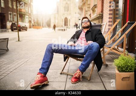 Une photo de jeune homme détente sur le transat au milieu de la place de la ville. Banque D'Images