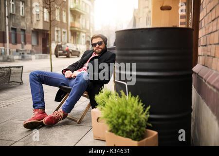Une photo du jeune homme assis sur le transat au milieu de la place de la ville. Banque D'Images