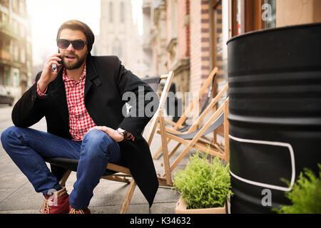 Une photo du jeune homme assis sur le transat au milieu de la place de la ville et de parler sur le mobile. Banque D'Images