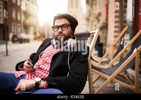 Une photo de jeune homme détente sur le transat devant certains cafe. Banque D'Images