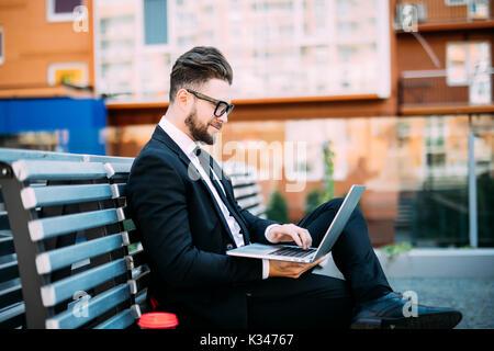 Man avec son ordinateur et de boire du café sur un banc Banque D'Images