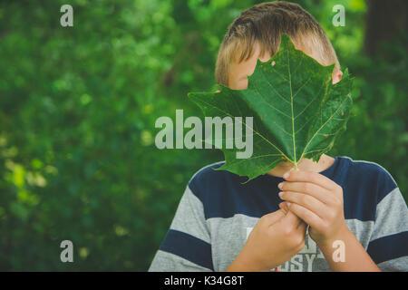 Un jeune garçon est titulaire d'une feuille verte en face de son visage. Banque D'Images