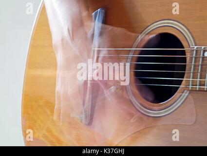 Close-up of a motion-main floue de gratter les cordes d'une guitare acoustique Banque D'Images