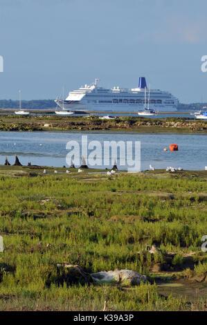 Un grand bateau de croisière ou d'un navire passant entrée de Newtown Creek à l'île de Wight de roseaux en premier Banque D'Images
