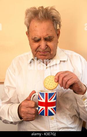 L'homme des personnes âgées diabétiques de type 2 manger un biscuit avec une tasse de thé Banque D'Images