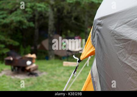 Un coin d'une tente, avec feu de camp, forêt et chaises de camping dans l'arrière-plan flou tente de camping et Banque D'Images