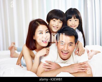 Happy asian famille avec deux enfants s'amuser au lit à la maison. Banque D'Images