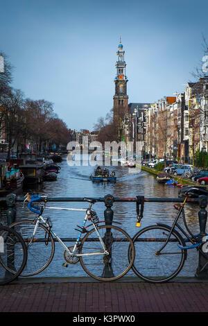 Amsterdam, Pays-Bas, Europe. Vélos garés sur le pont avec Westkerk en arrière-plan. Banque D'Images