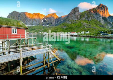 Soleil de minuit sur le village de pêcheurs et les pics entouré par la mer claire Reine Nordland County Lofoten, Banque D'Images