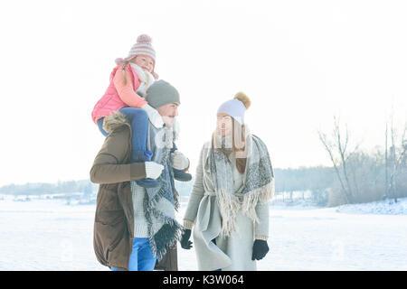 Les parents d'enfant en tant que famille en hiver en prenant une marche avec un piggyback ride
