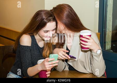 Deux filles potiner dans un café-bar Banque D'Images